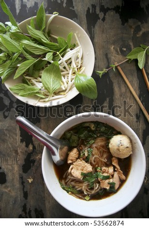 bowl of pungent thai pork noodle soup served with fresh sweet basil and beansprouts - stock photo