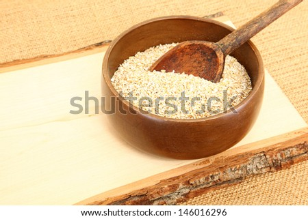 Bowl of Raw Steel Cut Oatmeal On Wooden Plank - stock photo