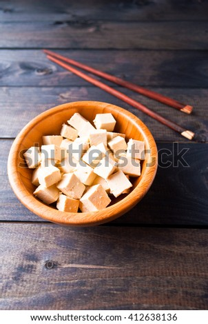 Bowl of raw tofu cubes and chopsticks on wooden background. Ingredient for vegan cuisine - stock photo