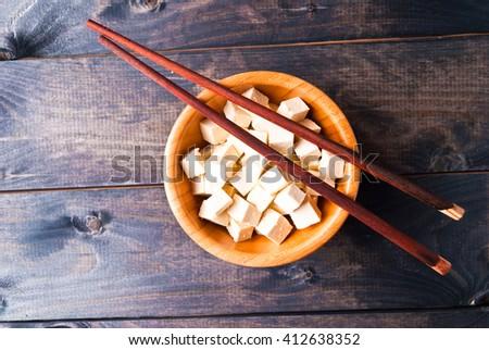 Bowl of raw tofu cubes and chopsticks. Top view - stock photo