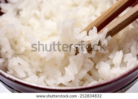Bowl of rice with chopsticks on white background - stock photo