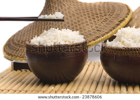 bowl of rice with oriental sticks and hats on bamboo - stock photo