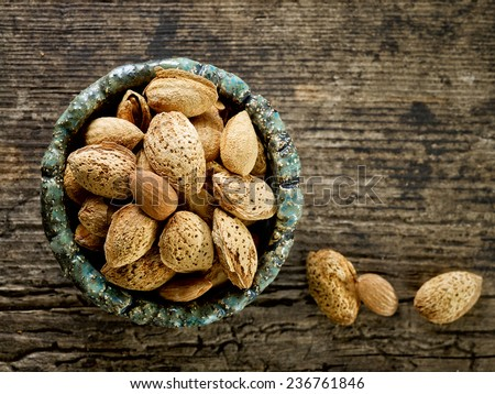 bowl of roasted almond nuts on old wooden table - stock photo