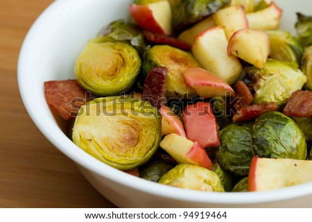 Bowl of roasted brussel sprouts with bacon and apple - stock photo