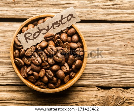 Bowl of Robusta coffee beans over an old wooden table - stock photo
