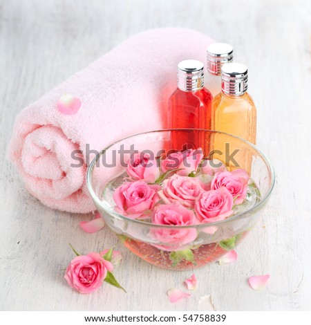 Bowl of roses, a towel and spa product - stock photo