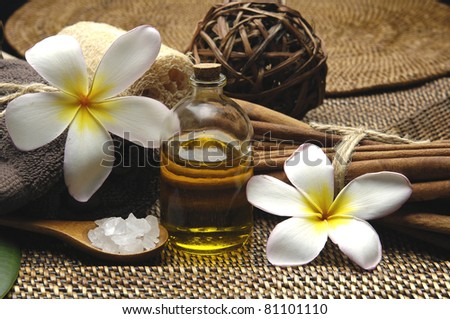 bowl of salt and frangipani with spa salt in bowl on burlap texture - stock photo