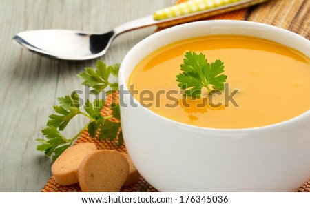 bowl of soup, parsley and croutons on wooden table - stock photo