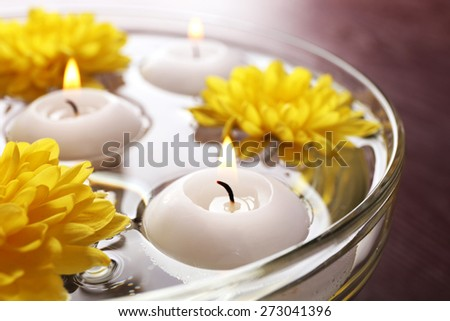 Bowl of spa water with flowers and candles on wooden table, closeup - stock photo
