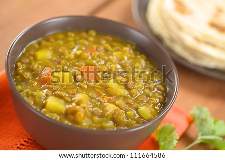 Bowl of spicy Indian dal (lentil) curry prepared with carrot and potato, chapati flat-bread in the back and cilantro leaf on the side (Selective Focus, Focus one third into the curry) - stock photo