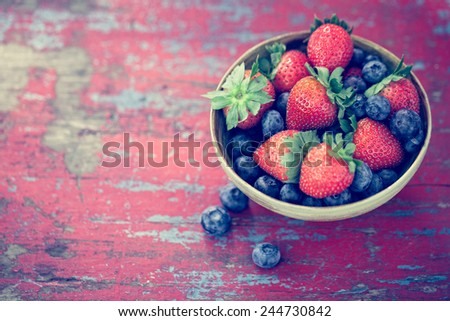 Bowl of strawberries and blueberries on vintage painted table - stock photo