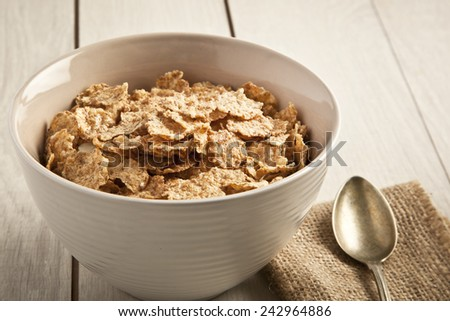 bowl of sugar-coated corn flakes and spoon wooden background - stock photo
