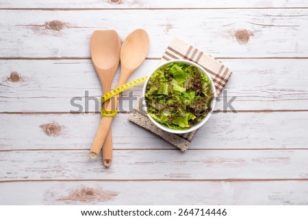 Bowl of Summer Salad. Fresh healthy salad on wooden table and kitchen utensil. View from above. bowl of leafy green salad with olives, tomatoes and cucumber. - stock photo