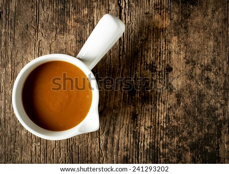 bowl of sweet caramel sauce on old wooden table - stock photo