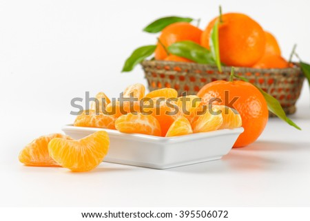 bowl of tangerine segments and whole tangerines on white background - stock photo