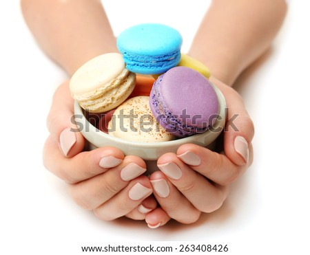 Bowl of tasty colorful macaroons in female hands isolated on white - stock photo