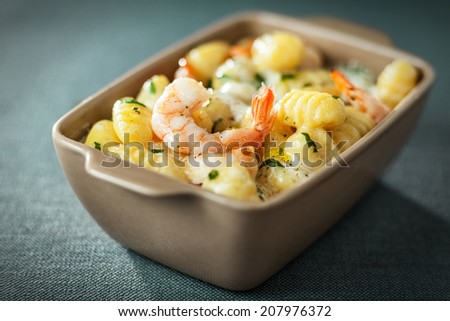 Bowl of tasty grilled prawns served with an aromatic sauce and fresh herbs in Italian gnocchi pasta for traditional Italian and Mediterranean cuisine - stock photo