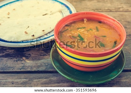 Bowl of tasty soup. Traditional meal with chapati bread. - stock photo