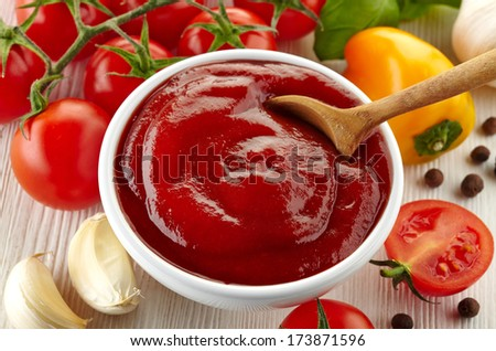 Bowl of tomato sauce with fresh ingredients on white wooden background - stock photo