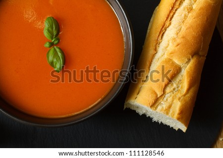 Bowl of tomato soup and basil garnish with bread baguette - stock photo