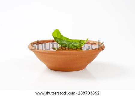 bowl of tomato soup and fresh basil on white background