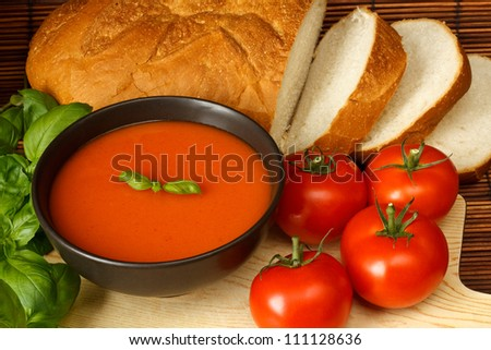 Bowl of tomato soup with basil garnish, in kitchen setting surrounded by ingredients - stock photo