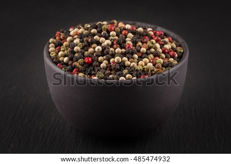 bowl of various pepper peppercorns seeds mix on dark stone