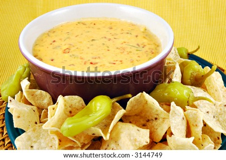 Bowl of warm queso (cheese dip) with a plate of tortilla chips - stock photo