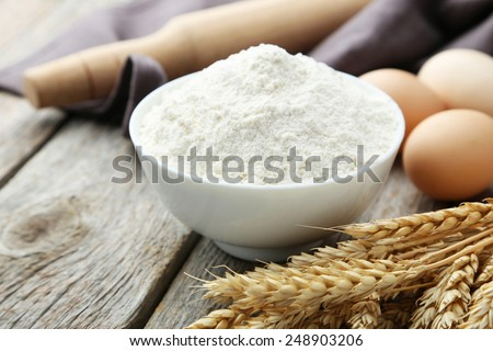 Bowl of wheat flour with spikelets on grey wooden background - stock photo