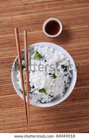 Bowl of white rice and soy sauce - stock photo