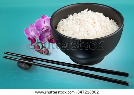 bowl of white rice, orchid and chopsticks - stock photo