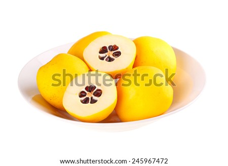 Bowl of whole and cut yellow, ripe fruit of the flowering or Japanese quince (Chaenomeles hybrids) isolated against a white background