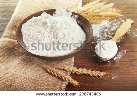 Bowl of whole flour with wheat ears on wooden table, closeup