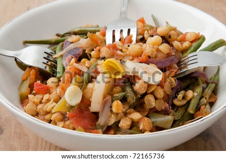 Bowl with a vegetarian tajine made from yellow peas, green beans, bell pepper, tomatoes, red onions, leek and apricots.