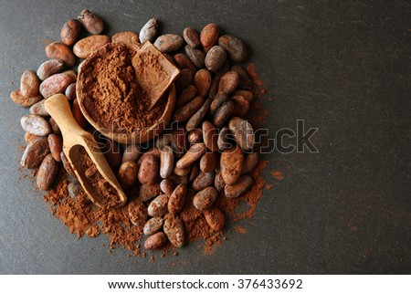Bowl with aromatic cocoa beans and chocolate on grey background, close up - stock photo