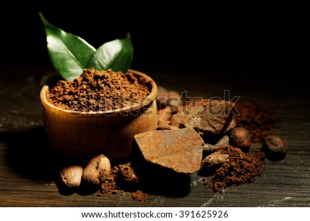Bowl with aromatic cocoa powder and green leaf on wooden background, close up - stock photo