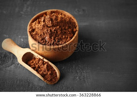 Bowl with aromatic cocoa powder on scratched wooden background, close up - stock photo