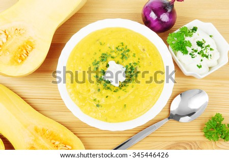 Bowl with butternut squash soup, a spoon, butternut squashes and a bowl of sour cream on wood