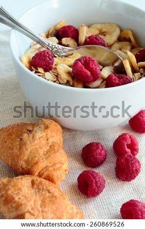 Bowl with cereals with fresh berries and croissants - stock photo