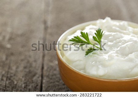 Bowl with cheese cream and parsley over wood background with copy space - stock photo