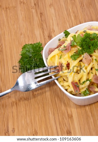 Bowl with Cheese Spaetzle and cutlery on wooden background - stock photo
