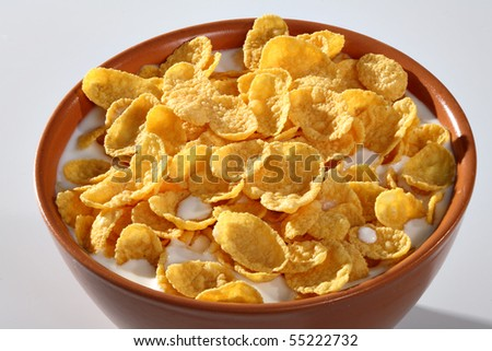 Bowl with corn flakes and milk on the white background - stock photo