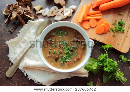 Bowl with fresh mushroom soup with parsley herbs - stock photo