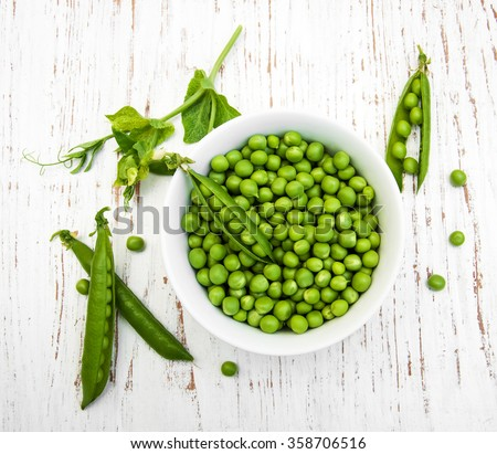 Bowl with fresh peas on a wooden background - stock photo