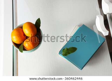 Bowl with fresh tangerines on table, close up - stock photo