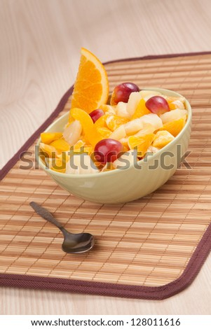 bowl with fruit salad with piece of orange and spoon - stock photo