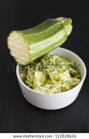 Bowl with grated zucchini and a half zucchini. - stock photo