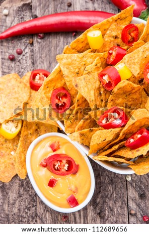 Bowl with Nachos and Cheese Sauce on wooden background - stock photo