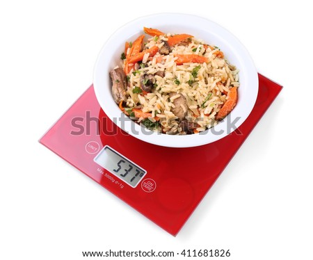 Bowl with pilaf on digital kitchen scales, isolated on white - stock photo