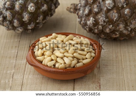 Bowl with pine nuts with pinoli, pine cones in the background